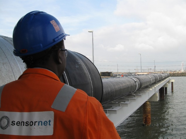worker looking at pipeline